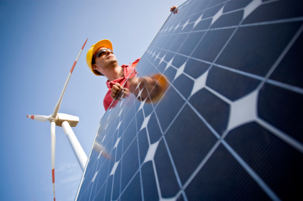 Image of a technician in between wind and solar technologies. In the background you can see Wind Turbines. Two different technologies to produce energy in a responsible and sustainable way.